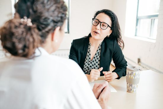 Student counselling: Counsellor with glasses and curly hair at her desk talking to a student with a ponytail. Photo: © kate_sept2004/E+/Getty Images