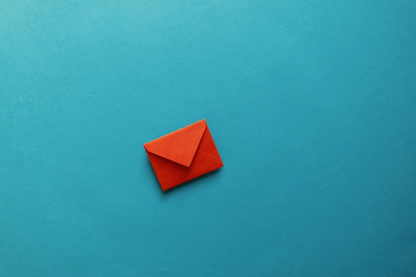 Application for your studies at the HWR Berlin: a small red envelope lies on a turquoise surface. Photo: © tolgart/iStock/Getty Images Plus