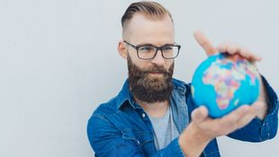 A bearded student in a blue denim shirt holds a small globe in both hands.  Photo: © stockfour/iStock/Getty Images Plus