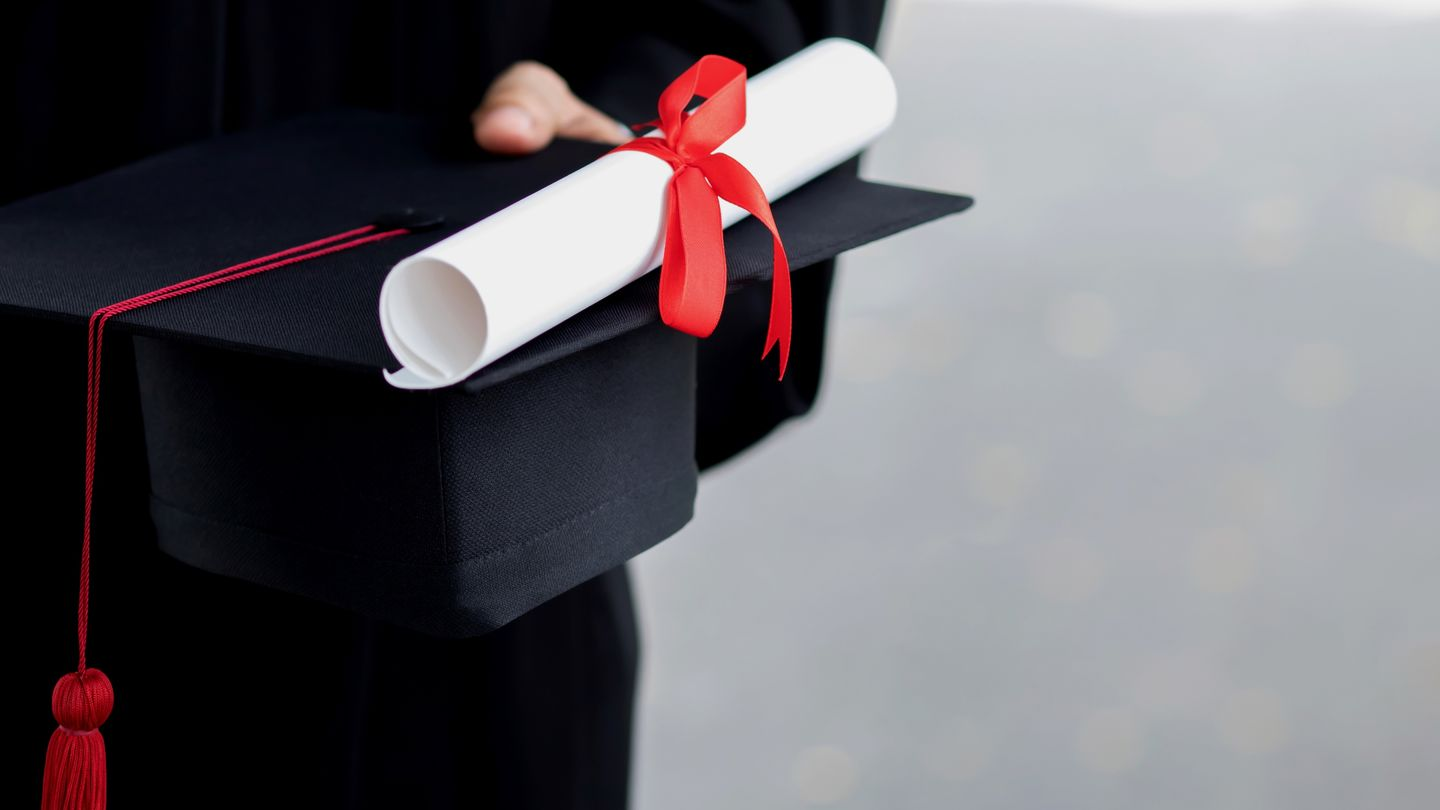 Degree: Graduate holds her Master's hat and Master's certificate in her hand. Photo: © Rattankun Thongbun/Getty Images/iStockphoto