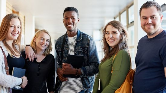 Applying for a Bachelor's degree at the HWR Berlin: Three female and two male students smile into the camera. Photo: © LumiNola/E+/Getty Images
