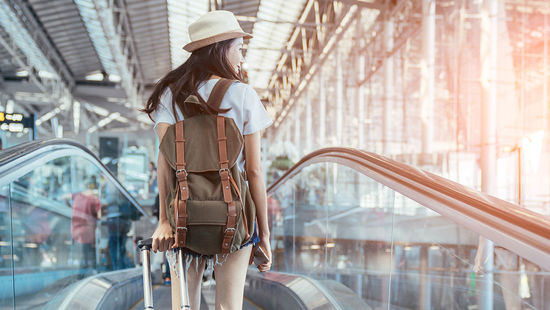 A female student with backpack and suitcase at the airport. Photo: Getty Images