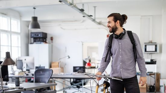 Application for dual studies: Dual student with beard, headphones around his neck and grey shirt pushing his bike in his company's office.