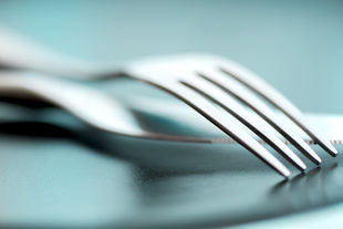 Close-up: a fork and a knife lying on a grey-blue surface.